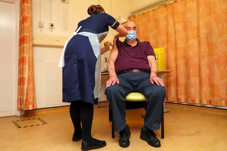 enfermeira de roupa preta e avental branco aplica vacina em homem de calça escura, blusa cor de vilho e máscara