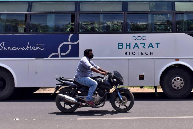 Homem trafega ao lado de ônibus da Bharat Biotech, laboratório indiano de vacinas