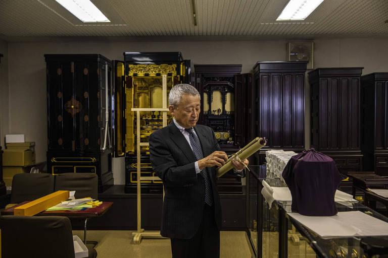 Um senhor japonês de terno e cabelo grisalho curto em uma loja