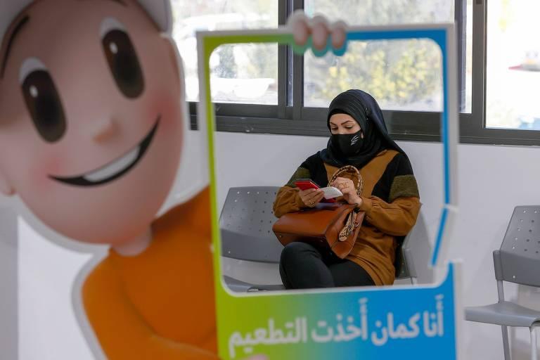 Mulher árabe aguarda para ser vacinada em centro de saúde na cidade israelense de Umm al Fahm