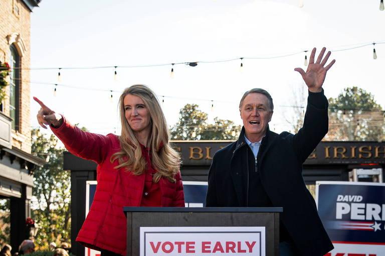 Os dois candidatos republicanos, os senadores Kelly Loeffler (esq.) e David Perdue, acenam após discursarem na cidade de Milton