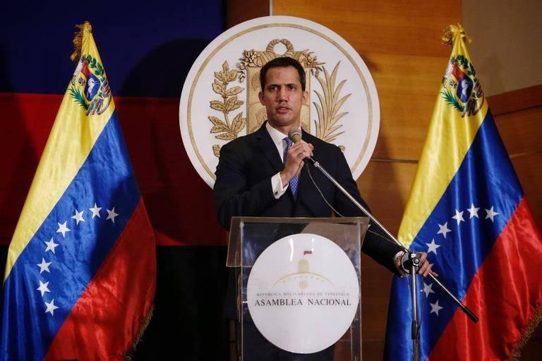 Juan Guaidó, de terno, segura microfone na frente de um púlpito, com duas bandeiras da Venezuela ao fundo