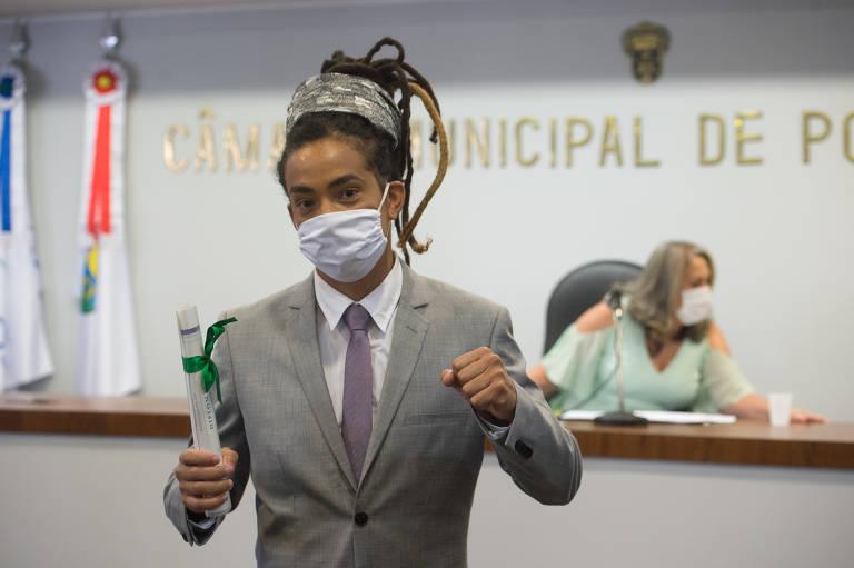 homem de terno e máscara segurando diploma