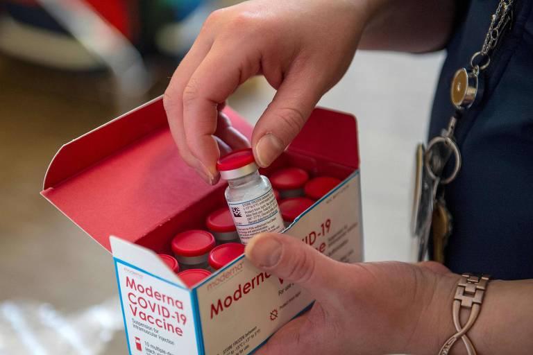 mão tira de caixa de vacinas uma ampola com tampa vermelha