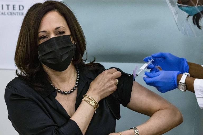 Mulher de blusa preta e máscara preta toma injeção no braço esquerdo