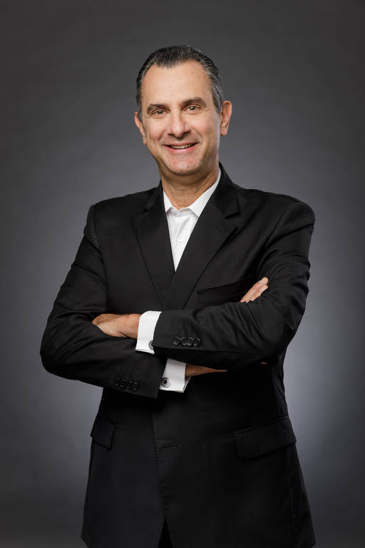 João Pedro Paro veste terno e sorri para a foto