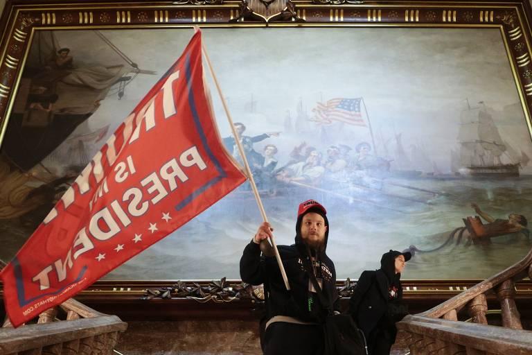 Manifestante segura uma bandeira em apoio a Donald Trump dentro do prédio do Congresso dos EUA, em uma área próxima à Câmara do Senado, em Washington