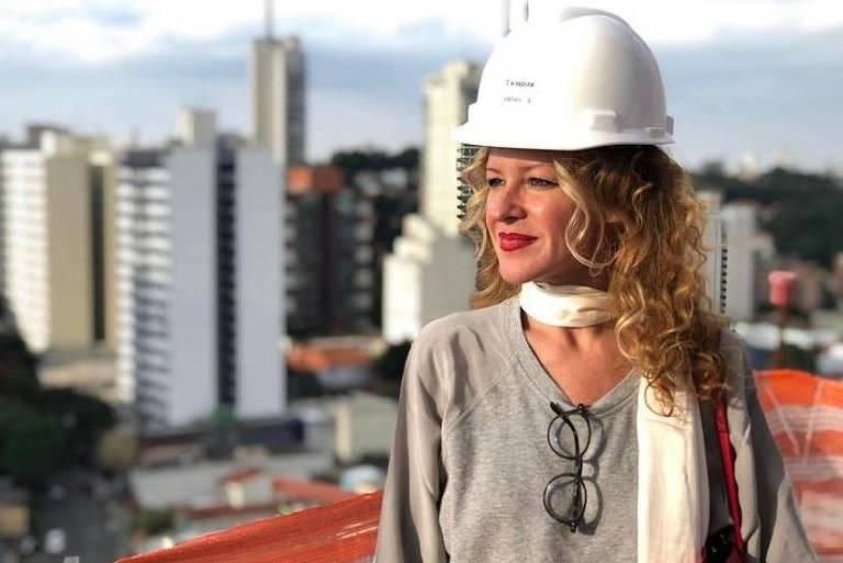 É uma mulher loira, de cabelos longos e cacheados, que se destacam sob o capacete branco de obra; ela usa uma malha cinza, uma echarpe branca, batom vermelho; pendurado na blusa, um par de óculos; ao fundo, vê-se uma paisagem de edifícios