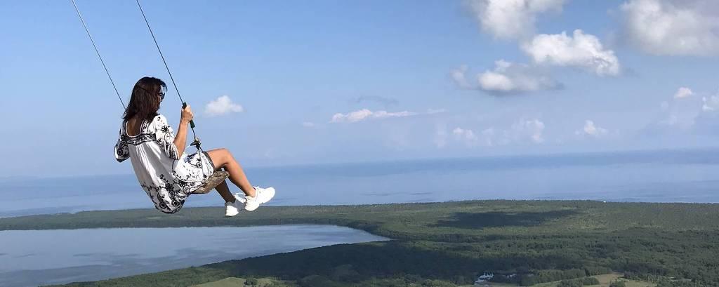 Mulher em balanço à beira da colina no pico da Montanha Redonda, próxima a Miches, na República Dominicana