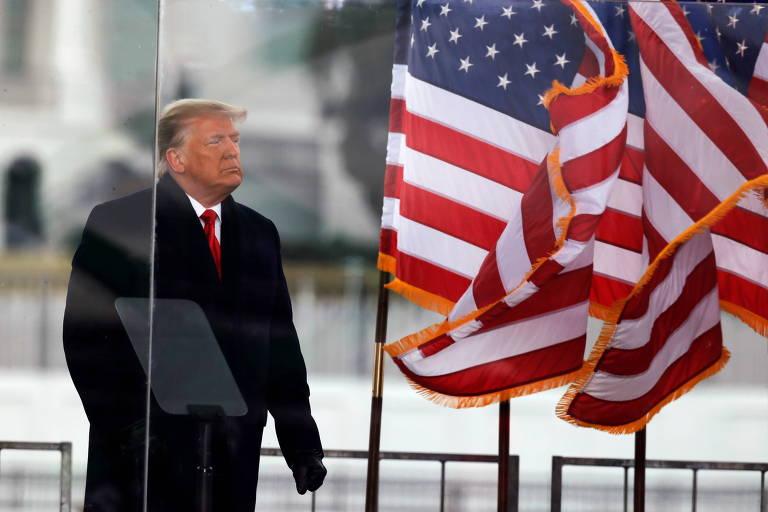 Donald Trump com a bandeira americana flamulando ao seu lado