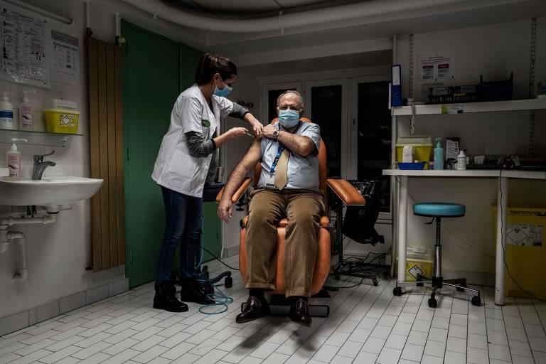 Enfermeira em pé injeta seringa com dose de vacina contra Covid-19 em paciente sentado numa cadeira dentro de uma sala