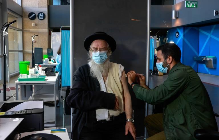 Profissional da saúde aplica vacina em judeu ultraortodoxo