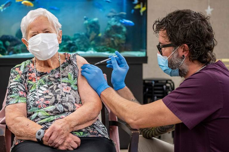 Idosa usando máscara de proteção recebe aplicação de vacina contra Covid-19