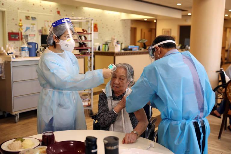 Idosa tem sua temperatura medida na testa enquanto recebe vacina em seu braço contra a Covid-19