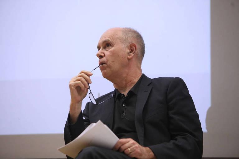 Homem de camisa preta segura folhas de papel e olha para o lado, com a haste dos óculos nos lábios