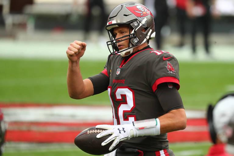 Tom Brady, de uniforme cinza, segura a bola com uma mão e vibra com a outra