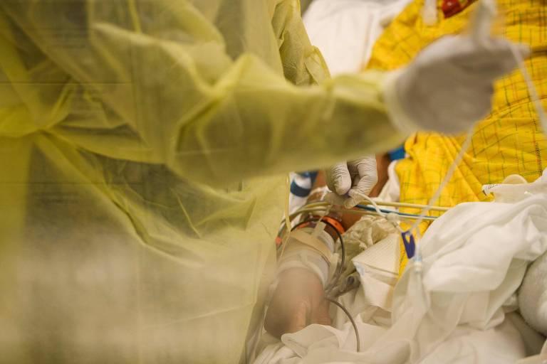 vultos de enfermeiros com aventais amarelos em volta de braço de paciente cheio de fios