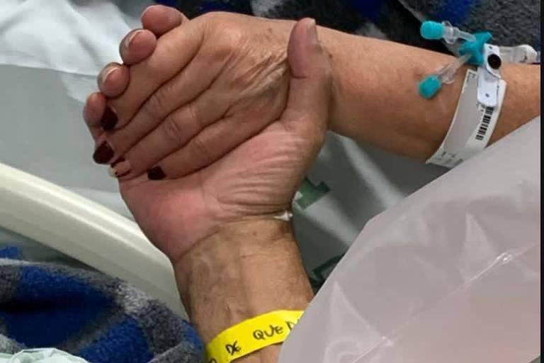Casal se dá as mãos em leito de hospital