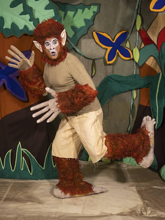 Ator está fantasiado como Curupira, peludo, com mãos gigantes e pés virados para trás