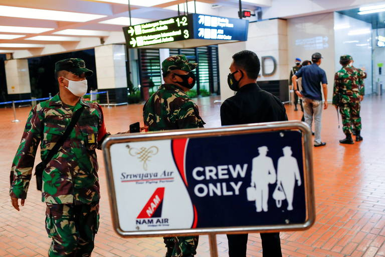 Soldados são vistos no Aeroporto Internacional Soekarno-Hatta neste sábado (9), após o desaparecimento de uma aeronave da companhia Sriwijaya Air