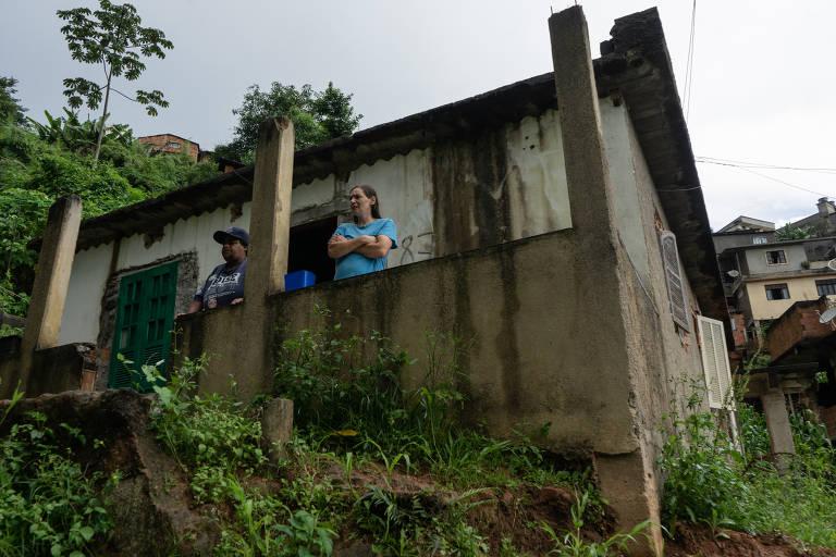 Moradores na varanda da casa, sem telhado