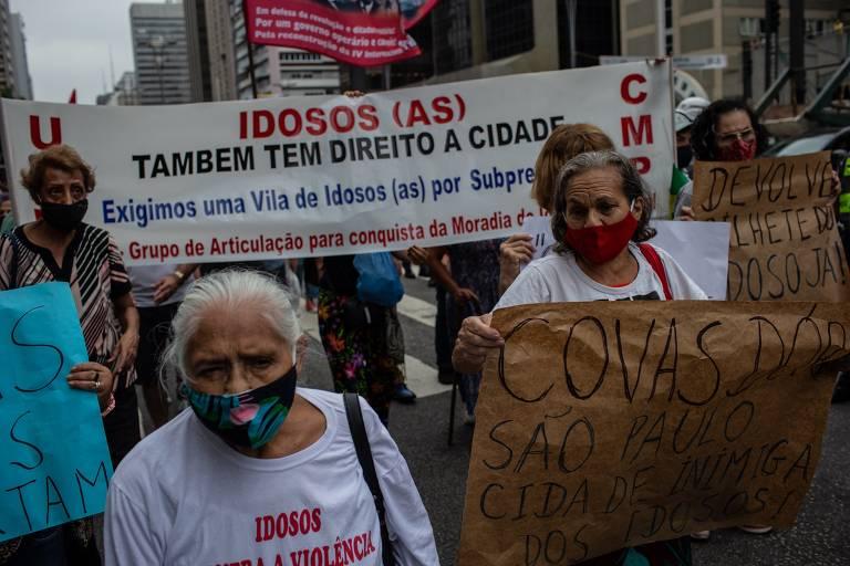 Idosas segurando cartazes caminham pela avenida Paulista em protesto a retirada do passe livre em São Paulo