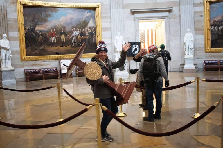 Adam Johnson carrega púlpito da presidente da Câmara dos Deputados, Nancy Pelosi, após invadir Capitólio