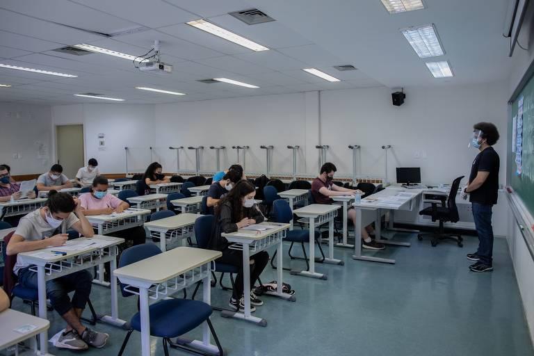 Visão da sala de aula inteira, com um fiscal na frente da sala e os estudantes já fazendo a prova