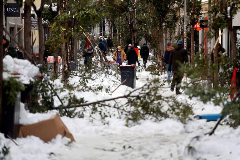 Moradores de Madri caminham em meio a galhos caídos em rua da capital da Espanha