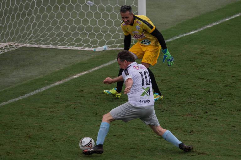 Bolsonaro, com uniforme branco, chuta bola para o gol observado por goleiro que veste amarelo