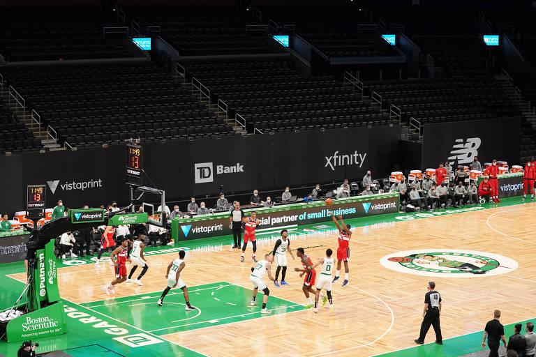 Foto aberta mostra jogando de vermelho arremessando da linha de três pontos