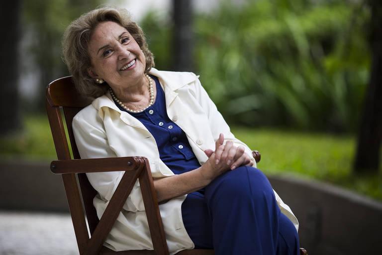 Mulher sentada em cadeira sorrindo para foto.