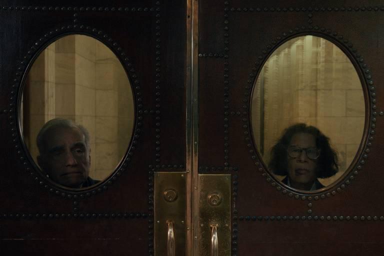 homem e mulher olham para o espectador por trás de portas com janelas ovais
