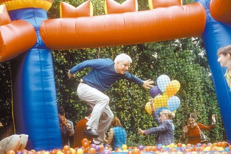 O ator de cabelos brancos pula na piscina de bolinhas como se fosse uma criança