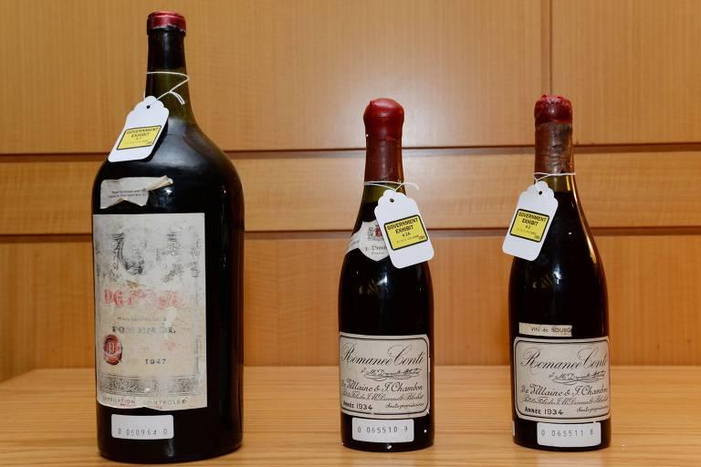 Três garrafas de vinho aparentando serem bem antigos