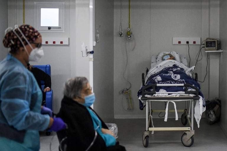 Enfermeira empurra cadeira de rodas de paciente com Covid-19 em pronto socorro de hospital de Lisboa
