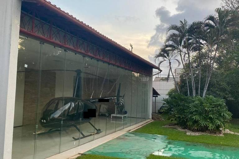 Helicóptero dentro da garagem de uma residência por trás de uma proteção de vidro