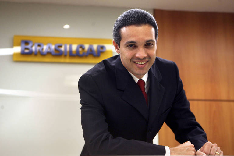 De terno escuro, Márcio posa para a foto diante da placa Brasilcap