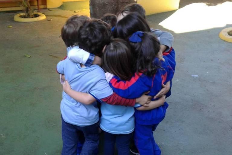 Seis crianças se abraçam em um círculo vestindo uniforme escolar