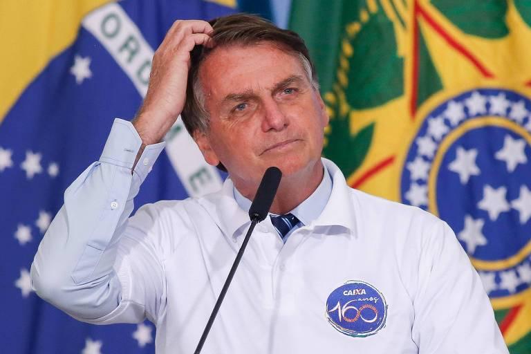 Diante de duas bandeiras, Bolsonaro posicionado ao microfone com uma mão na cabeça