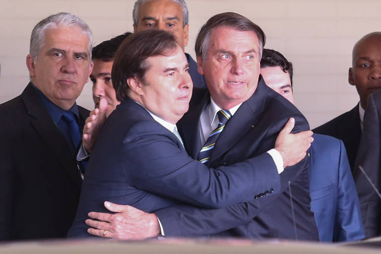 O presidente da República, Jair Bolsonaro, e o presidente da Câmara dos Deputados, Rodrigo Maia, abraçam-se. Ao fundo outros políticos.