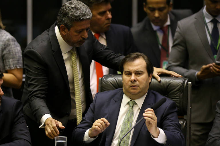 Rodrigo Maia, presidente da Câmara dos Deputados, está sentado em uma cadeira preta e tem expressão de estranheza. Falando com ele, o deputado Arthur Lira está de pé, ao seu lado.