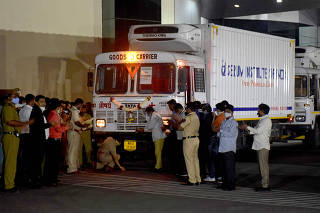 A police officer performs prayers in front of a truck carrying first consignment of COVISHIELD before it leaves from Serum Bio-Pharma Park of Serum Institute of India, to be distributed, in Pune