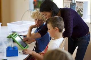 A teacher explains a math problem to students on their iPads at the Steve Jobs school in Sneek