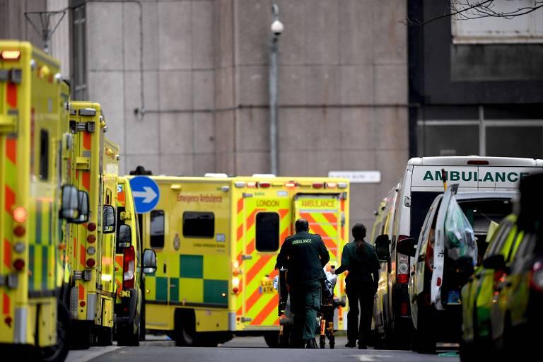 Paramédicos levam paciente em meio a fila de ambulâncias em Londres