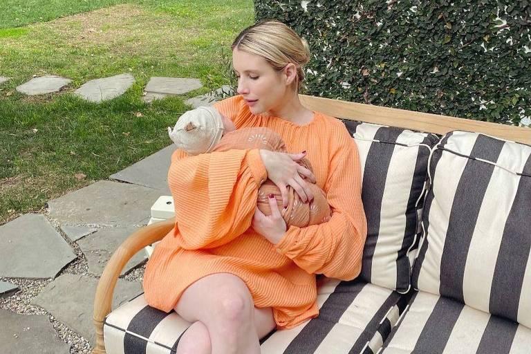 Emma Roberts segura seu filho no colo, usando vestido e sapato de salto laranja enquanto está sentada em um sofá com listras brancas e pretas