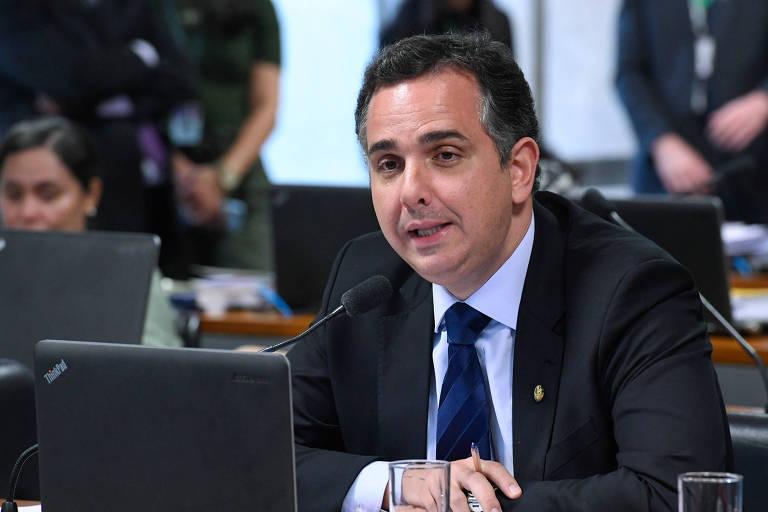 Pacheco numa bancada falando ao microfone da mesa diante de uma tela de computador