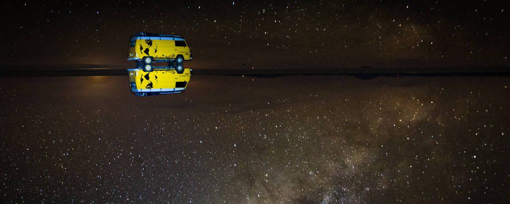 Kombi amarela em meio a deserto à noite. O chão espelhado reflete o céu estrelado