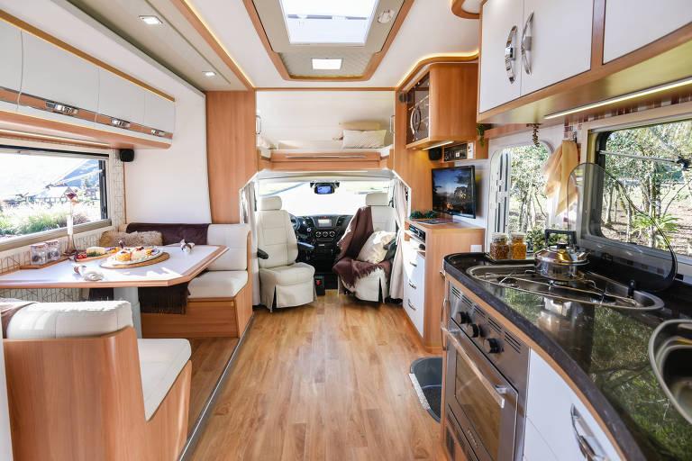 Interior do motorhome com sala de estar, de jantar e cozinha, tudo com piso e acabamentos de madeira