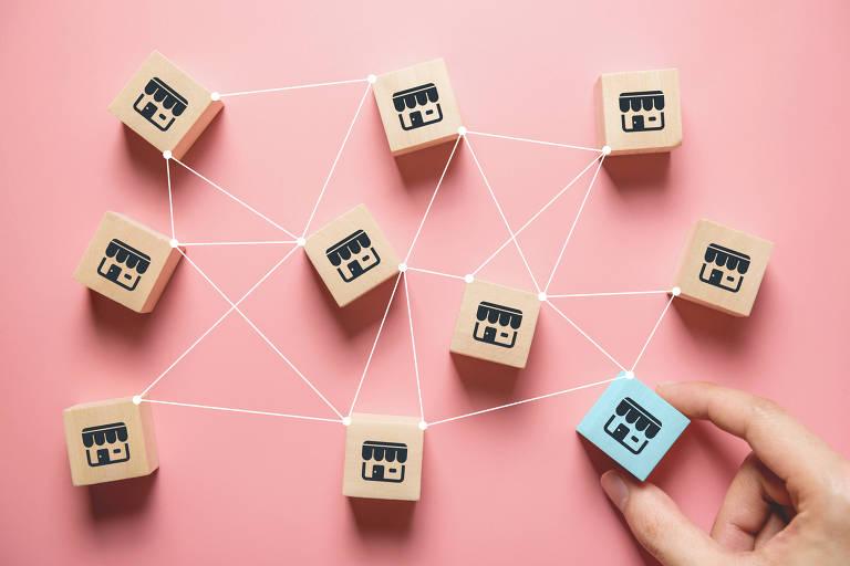 Sobre fundo rosa há vários quadrados com desenho de fechada de loja, interligados com fios, como em uma rede